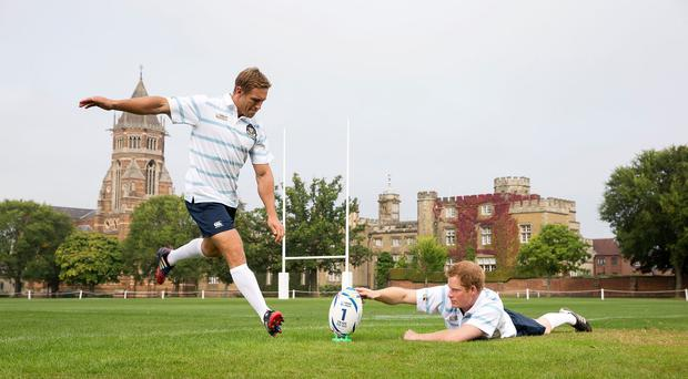 Prince Harry, right, helps Rugby World Cup 2003 winner and England 2015 Ambassador Jonny Wilkinson take a kick