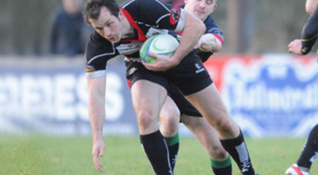 Holding on: Clogher Valley do their utmost to stop Cooke ace Graham Dewhurst in his tracks