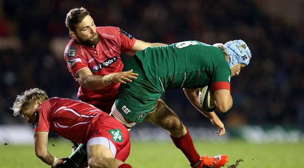 Leicester Tigers' Jordan Crane is tackled by Scarlets' Aled Davies and John Barclay during the European Champions Cup Pool Three match at Welford Road, Leicester.