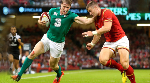 Arm's length: Andrew Trimble holds off Wales' Scott Williams