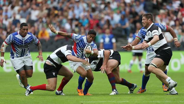Samoa's Ken Pisi is tackled by Barbarians' Liam Gill and Carl Hayman during the Test Match at The Stadium at Queen Elizabeth Olympic Park, London.