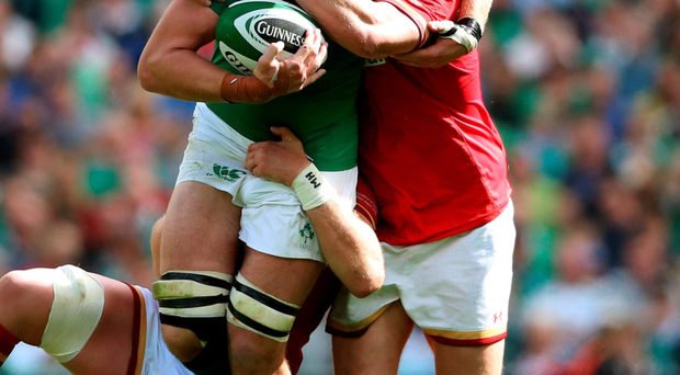 Fighting through: Ireland's Iain Henderson is tackled by Wales' Gethin Jenkins (right) and captain Alun Wyn Jones