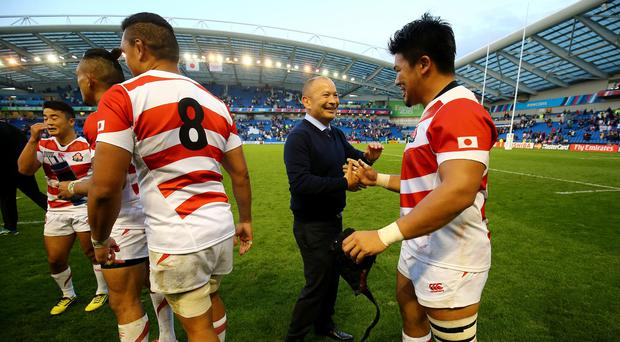 Japan coach Eddie Jones congratulates his team after their extraordinary win