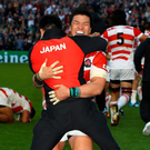 World beaters: Japanese players celebrate their victory over South Africa in Brighton on Saturday
