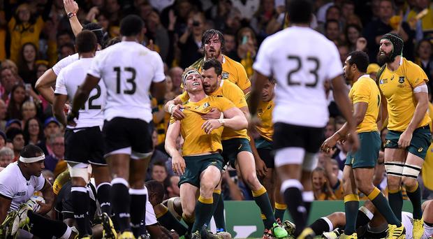 Australia's David Pocock is congratulated by team-mates after scoring a try in their victory over Fiji