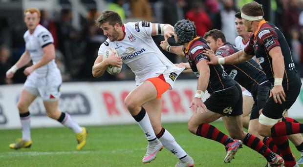Holding on: Ulster ace Stuart McCloskey gets shirty with the Dragons defence as he embarks on a surging run