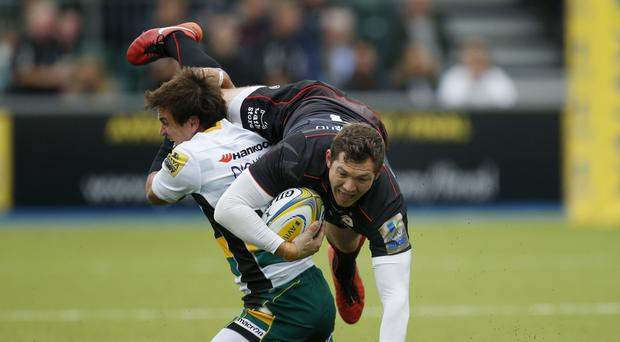 Northampton Saints' Lee Dickson (left) tackles Saracens' Alex Goode at Allianz Park