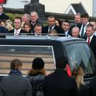Mourners look on as Anthony Foley's coffin arrives at St Flannan's Church, Killaloe, Co. Clare
