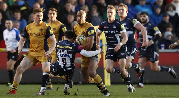 Tom Varndell, centre, goes past Sale's James Mitchell to score a try