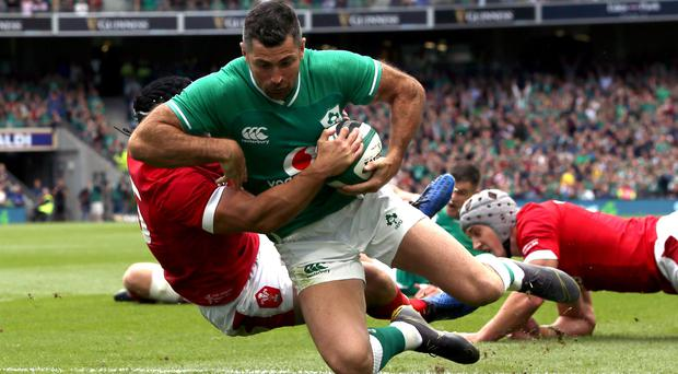 Ireland's Rob Kearney (right) goes passed Wales' Leigh Halfpenny (left) to score his side's opening try (Brian Lawless/PA).