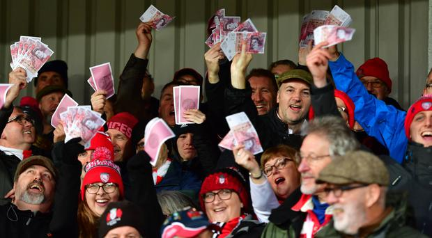 Gloucester fans waving fake money and wearing caps during the Gallagher Premiership match against Saracens (Simon Galloway/PA)