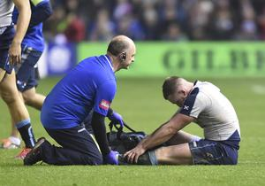 Stuart Hogg of Scotland gets treatment from Scotland team doctor Dr James Robson (PA)