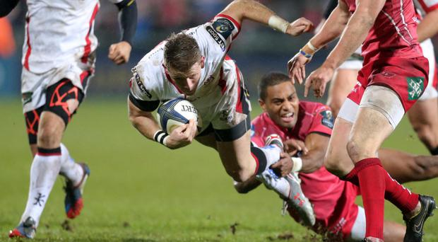 Falling down: Ulster winger Craig Gilroy is brought to ground during Saturday night's European win over the Scarlets