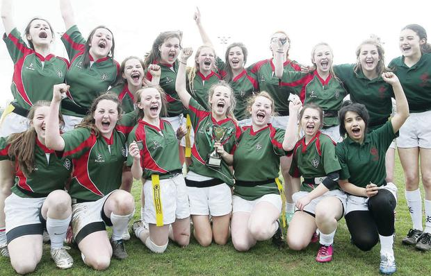 Enniskillen Collegiate celebrate Schools' Cup win at Queen's Arena while Grosvenor's Chloe McMaster tries to get past Kathryn Dane (left) and Alison Glass