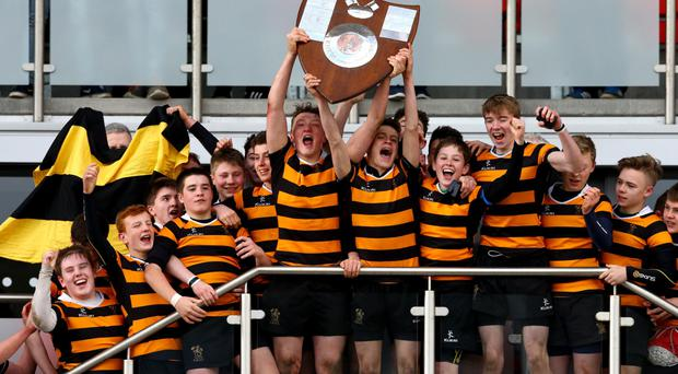 First class honours: RBAI's captain Ethan Glover gets the party started by lifting the Danske Bank Medallion Shield