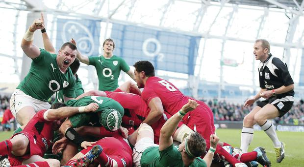 Green machine: Cian Healy celebrates Chris Henry's try in Ireland's comprehensive thumping of Wales