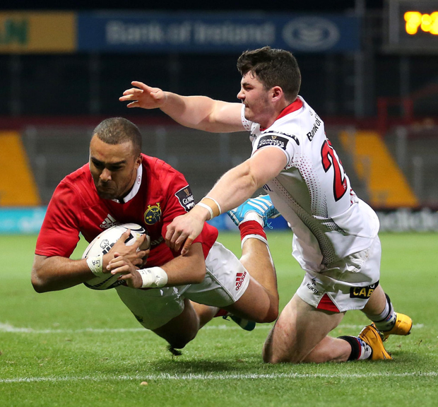High five: Simon Zebo scores Munster's fifth try against Ulster at Thomond Park despite the attentions of Sam Arnold