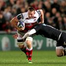 Running man: Ulster's Jean Deysel charges through the challenge of Wasps' Elliot Daly
