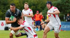 Going down: Munster's Jack O'Sullivan is tackled by Ethan McIlroy of Ulster