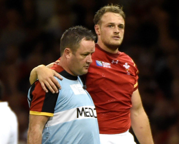Crocked: Wales' centre Cory Allen leaves the field injured