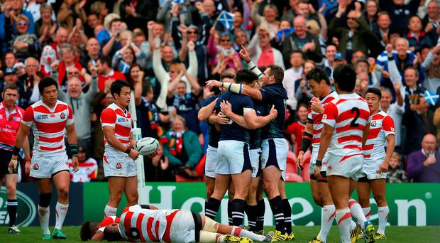 Third man: The Scotland team celebrate after Mark Bennett scores their third try of the game against Japan