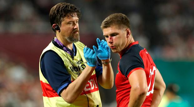 Early bath: Owen Farrell of England receives medical treatment after the incident in which John Quill of the USA was sent off