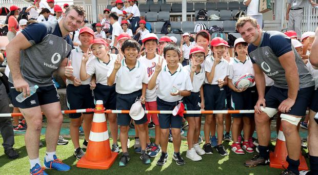 Fan power: Peter O'Mahony and Jordi Murphy meet some young fans during yesterday's training session in Kobe