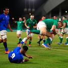 Flying high: Jordan Larmour of Ireland scores his team's fifth try past Dwayne Polataivao of Samoa