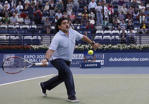 Soccer legend Diego Maradona of Argentina plays tennis with country man Juan Martin Del Potro alongside the Dubai Duty Free Tennis Championships in Dubai, United Arab Emirates Wednesday, Feb. 27, 2013. (AP Photo/Regi Varghese)