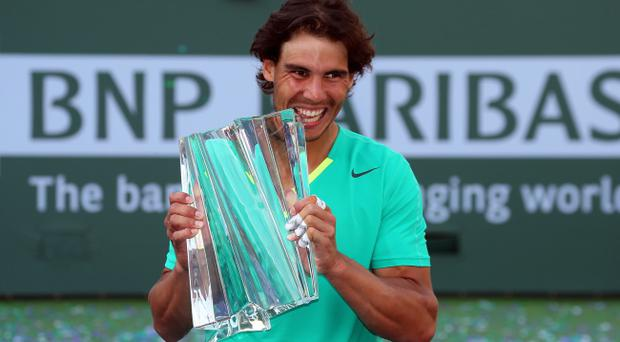 INDIAN WELLS, CA - MARCH 17: Rafael Nadal of Spain celebrates with the trophy after defeating Juan Martin Del Potro of Argentina to win the men's final match of the 2013 BNP Paribas Open at the Indian Wells Tennis Garden on March 17, 2013 in Indian Wells, California. (Photo by Stephen Dunn/Getty Images)