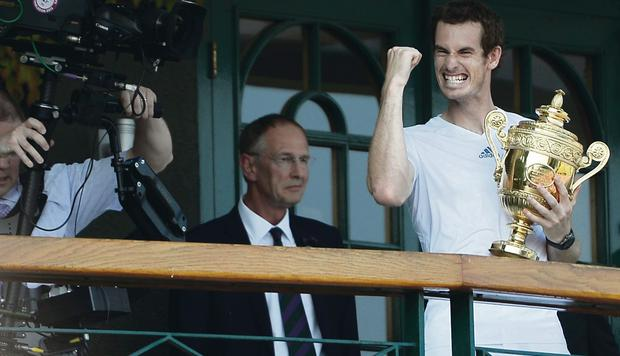Andy Murray of Great Britain punches the air on the Centre court balcony as he holds the Gentlemen's Singles Trophy following his victory in the Gentlemen's Singles Final match against Novak Djokovic of Serbia on day thirteen of the Wimbledon Lawn Tennis Championships