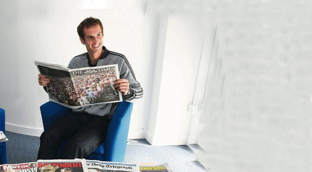 Andy Murray of Great Britain reads through the morning papers at Wimbledon on July 8, 2013