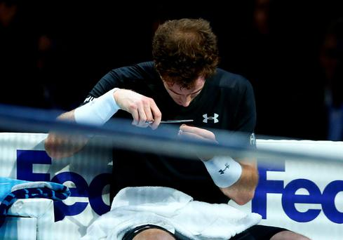 Growing pains: Andy Murray cuts his hair during the match
