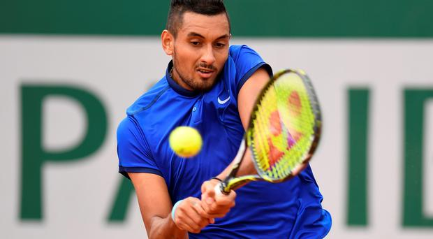 Winning start: Nick Kyrgios hits a backhand during his first round match against Marco Cecchinato at Roland Garros