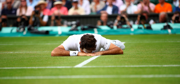 Going, going, gone: Roger Federer falls to the ground after giving Milos Raonic the chance to break at a crucial moment during the fifth and deciding set of his semi-final defeat at SW19