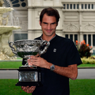 Champion: Roger Federer poses with the Australian Open trophy following his epic game with old rival Rafael Nadal on Sunday