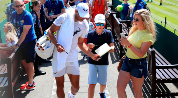 Sign here: Rafael Nadal gives a young fan his autograph