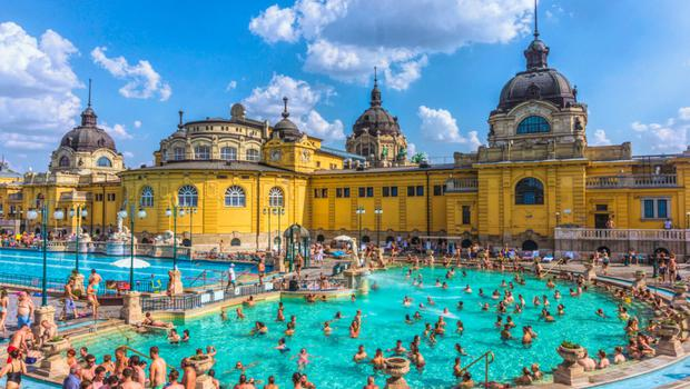 Budapest, Hungary - August 30, 2019: Famous Secheni Thermal Pools in Budapest, Hungary. Having fun and bathing people. Wellness complex of public therapeutic pools and saunas for water treatments. Budapest ancient tourist attraction