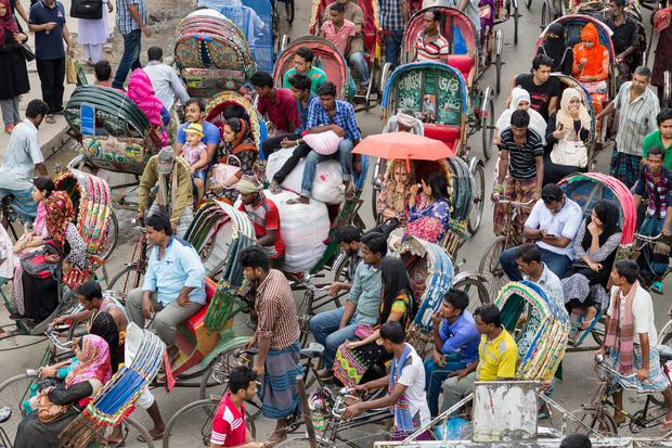 Locals stuck in a cycle rickshaw traffic jam in a busy street in Dhaka.