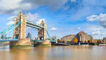 Tower Bridge in London, England, on a bright sunny day under gorgeous sky with clouds.