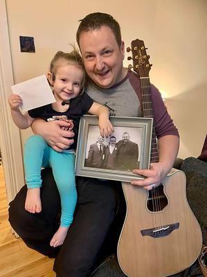 Stephen with his daughter holding a photo of late pal Martin O'Donnell
