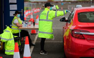 A member of staff hands over a Randox laboratories Covid-19 self test kit to a member of the public at a drive-through test centre at the SSE Arena in Belfast. PA