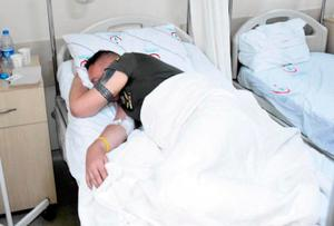 Ian Campbell lying in hospital bed.