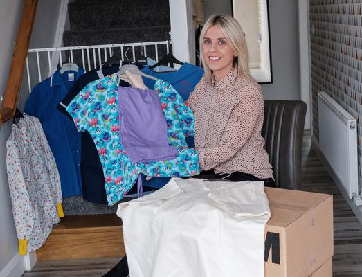 Clara Maybin pictured at her home with some of the garments made by thousands of volunteers which will be used by the NHS.