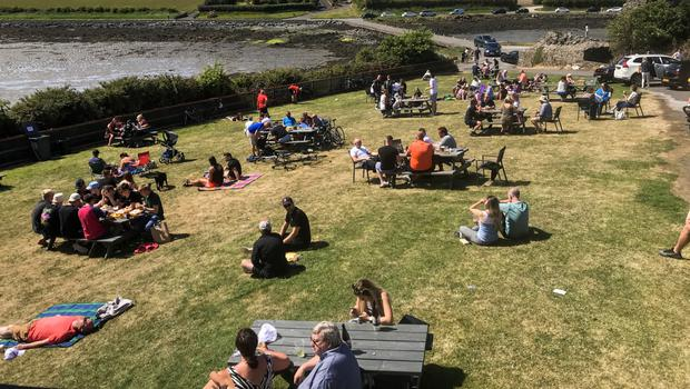 Lazy summer days: Punters enjoy drinks next to Daft Eddy's Bar & Restaurant, Sketrick Island, Killinchy, Co Down