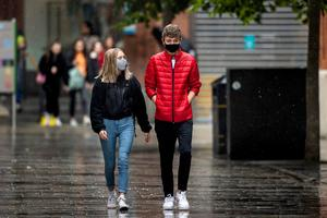 Laura Copeland (left) and Daniel Gorman through Belfast City Centre's shopping district wearing a face mask. Picture: Liam McBurney/PA Wire