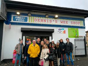Helen Carson with visitors on Derry Girls tour outside Dennis' Wee Shop with a tour guide from Martin McCrossan tours.