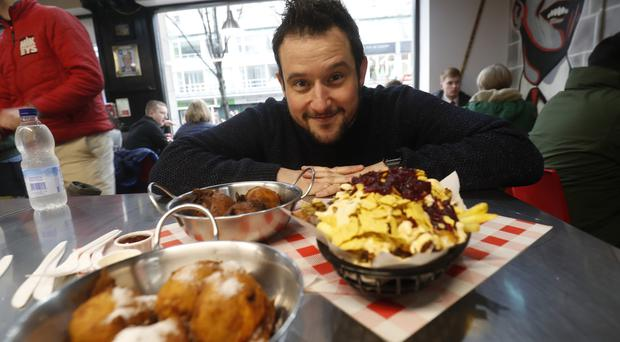 John Toner at Mikeys Deli eating the Christmas Bronx with battered Oreos. Pictured is Mikeys Owner Michael Curran. (red Coat). PIcture Colm O'Reilly 04-12-2019 Sunday Life