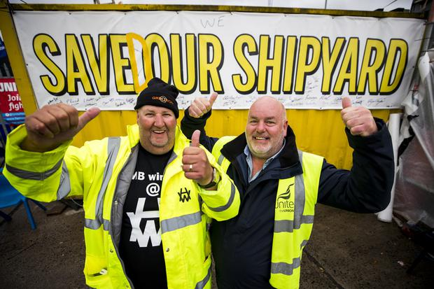 Harland and Wolff workers Barry Reid (left) and Joe Passmore celebrate following the announcement that the Belfast shipyard has been saved after it was bought for £6 million by InfraStrata, a company that works on energy infrastructure projects.