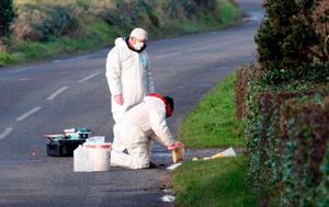 SEARCH: Forensics examine an area near where Philip Strickland was gunned down